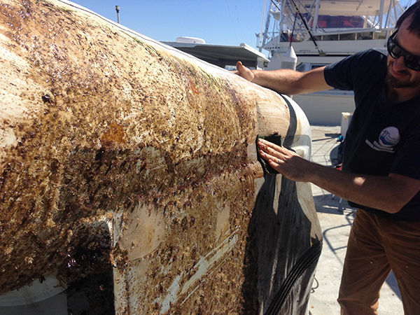 Jonah cleaning and repairing our dinghy